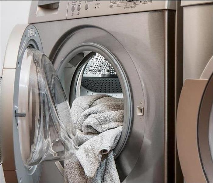 An open washing machine with a towel sticking out
