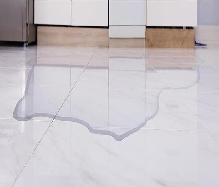 A white tile floor with water on it.