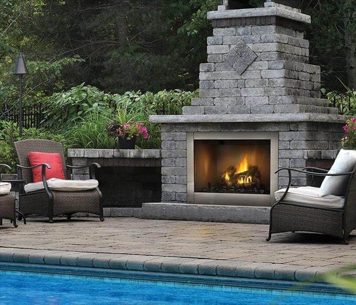 Outside space with chairs and lit fireplace.